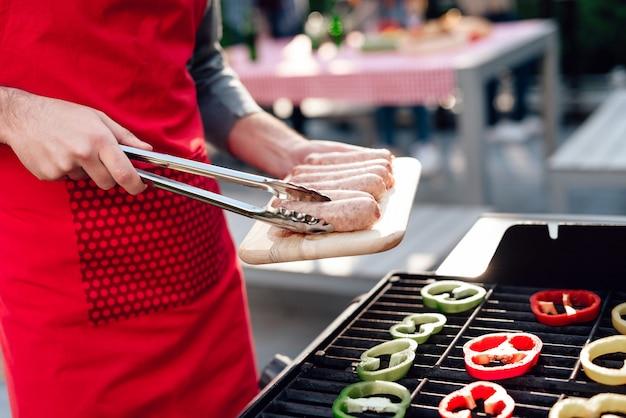 De mens kookt worsten op de grill op een feestje van vrienden. Premium Foto