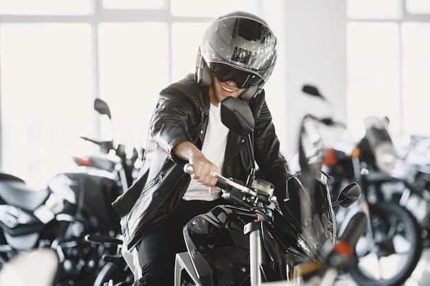 De mens koos voor motorfietsen in de moto-winkel. man in een zwart jasje. man in een helm. Gratis Foto