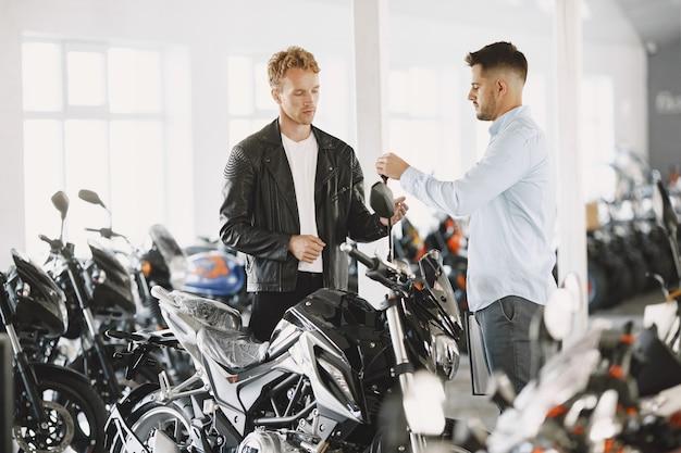 De mens koos voor motorfietsen in de moto-winkel. man in een zwart jasje. manager met klant. Gratis Foto