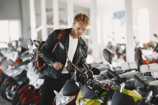 De mens koos voor motorfietsen in de moto-winkel. man in een zwart jasje. Gratis Foto