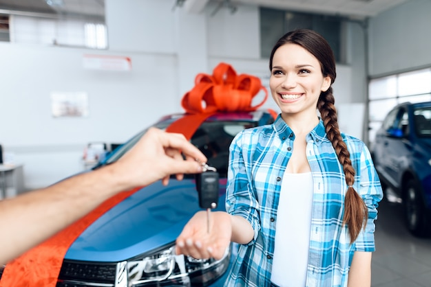 De mens maakt een geschenk - auto aan zijn vrouw. ze is hier verbaasd over Premium Foto