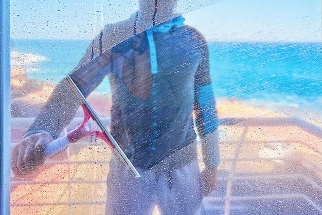 De mens maakt vuil glasvenster met wisserborstel binnen mening schoon Premium Foto