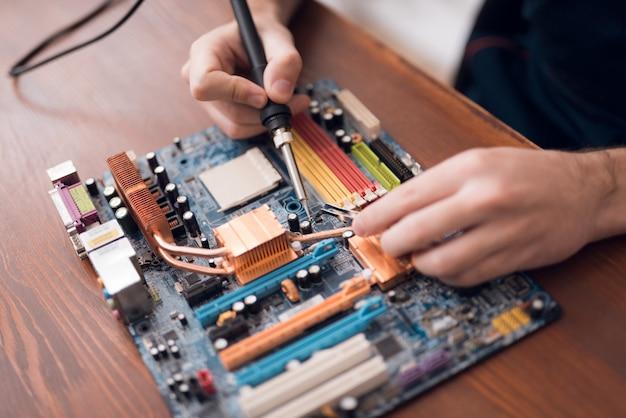 De mens met een soldeerbout herstelt computerapparatuur. Premium Foto