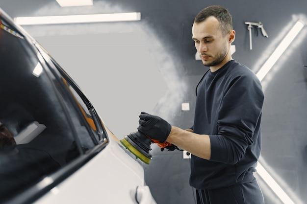 De mens poetst een auto in een garage op Gratis Foto