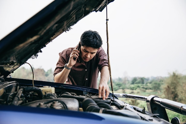 De mens probeert een motor van een motorprobleem op een lokale weg te bevestigen Gratis Foto