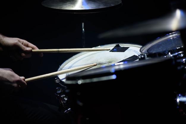 De mens speelt muzikaal slaginstrument met stokkenclose-up, een muzikaal concept met de werkende trommel, mooie verlichting op het stadium Premium Foto