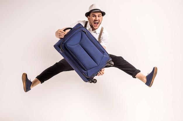 De mens stelt met koffer Premium Foto