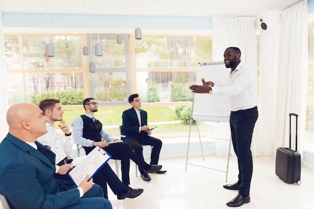 De mens toont iets aan zijn collega's in de wachtkamer. Premium Foto