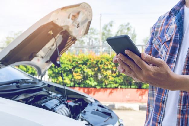 De mens van azië bevindt zich voor een gebroken auto die hulp verzoeken Premium Foto
