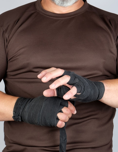 De mens verpakt zijn handen in zwart textielverband voor sporten Premium Foto