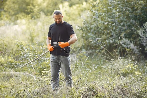 De mens verzamelt bladeren en maakt het park schoon Gratis Foto