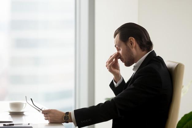 De mens voelt moeheid in ogen na het werk in bureau Gratis Foto