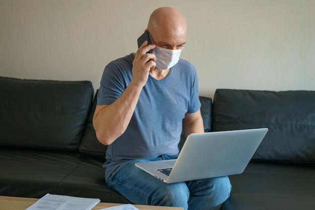 De mens zit op een bank in een beschermend masker met laptop en telefoon, het verre werk in quarantaine Premium Foto