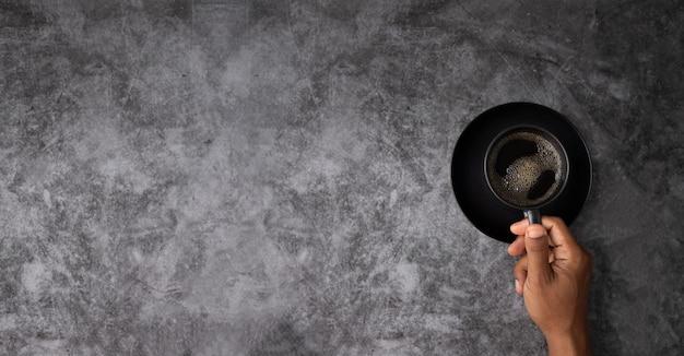 De menselijke kop van de hand zwarte koffie met copyspace op de achtergrond van de de muurtextuur van het grungecement met linkerexemplaarruimte. Premium Foto