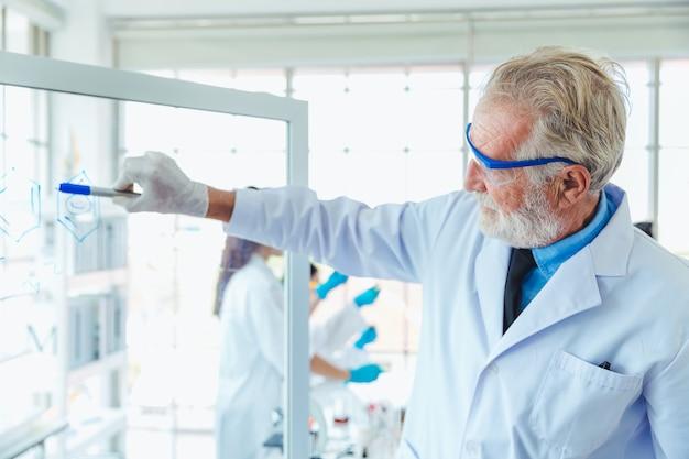 De mensen die van de wetenschapsleraar met de transparante chemische producten van de glasraad in laboratorium werken Premium Foto