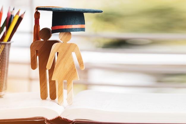 De mensen ondertekenen hout met graduatie het vieren glb op open handboek Premium Foto
