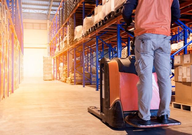 De mensenarbeider werkt met elektrische vorkheftruck in pakhuisfabriek. Premium Foto