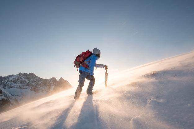 De mensenfotograaf met driepoot beklimt op hellingsheuvel met blizzard Premium Foto