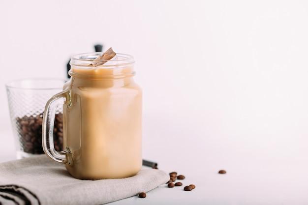 De metselaarkruik van het glas met ijskoffie met melkachtergrond Premium Foto