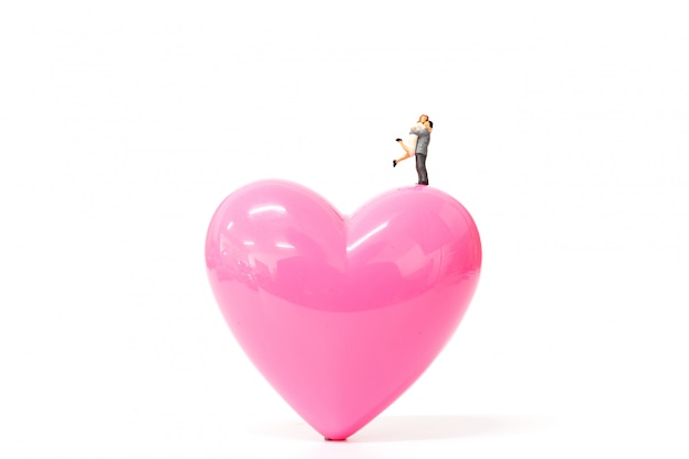 De miniatuurmensen koppelen aan roze hart op witte achtergrond Premium Foto