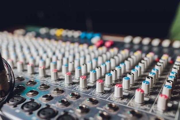 De mixer. afstandsbediening voor geluidsopname. geluidstechnicus aan het werk in de studio. geluidsversterker mengpaneel equalizer. liedjes en zang opnemen. tracks mixen. geluidsapparatuur. werken met muzikanten. dj. Premium Foto