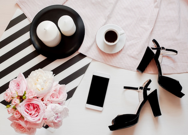 De modeaccessoires van de vrouw, smartphonespot omhoog, boeket van rozen en pionen, schoenen Premium Foto