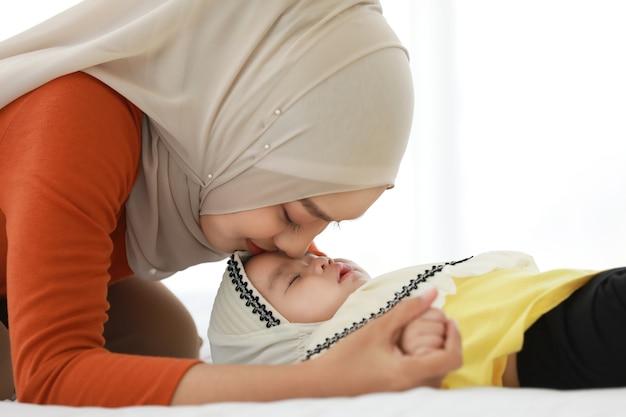 De moeder draagt een hoofddoek en ligt naast de baby op bed. Premium Foto