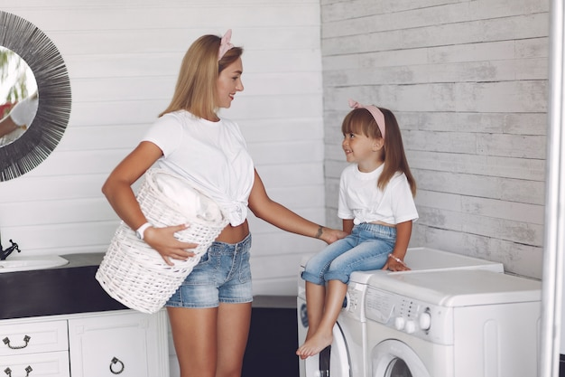 De moeder en de dochter in een badkamers wassen dichtbij mashine Gratis Foto