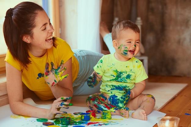 De moeder en zoon schilderen een groot papier met hun handen Gratis Foto
