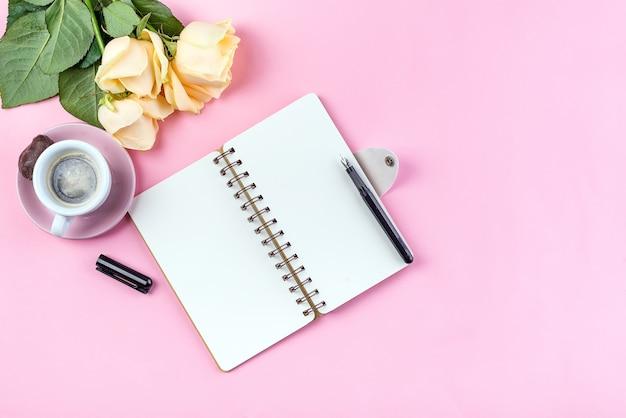 De mok van de ochtendkoffie voor ontbijt, leeg notitieboekje, potlood en nam op de roze mening van de lijstbovenkant toe Premium Foto