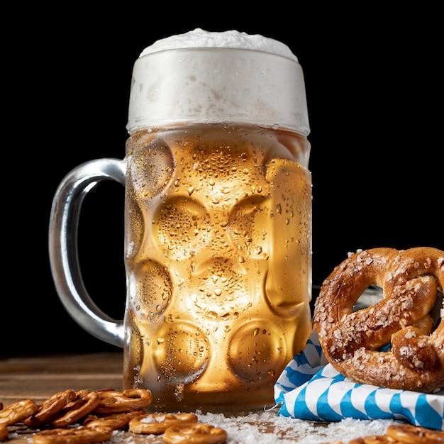 De mok van het close-upbier met schuim en pretzels Gratis Foto