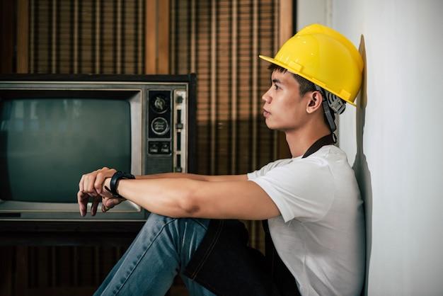 De monteur draagt een gele hoed en de handen rusten op de knieën. Gratis Foto
