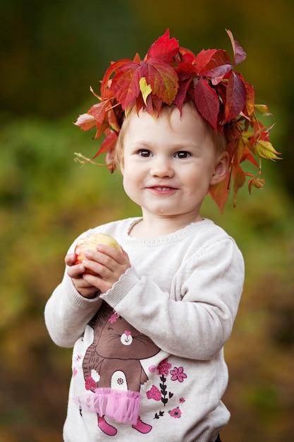 De mooie appelen van de meisjeholding in de de herfsttuin. klein meisje spelen met appels. halloween en thanksgiving tijd leuk voor familie. Premium Foto