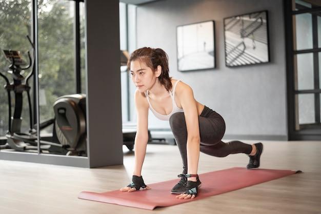 De mooie aziatische vrouw doet oefening in de gymnastiek Premium Foto