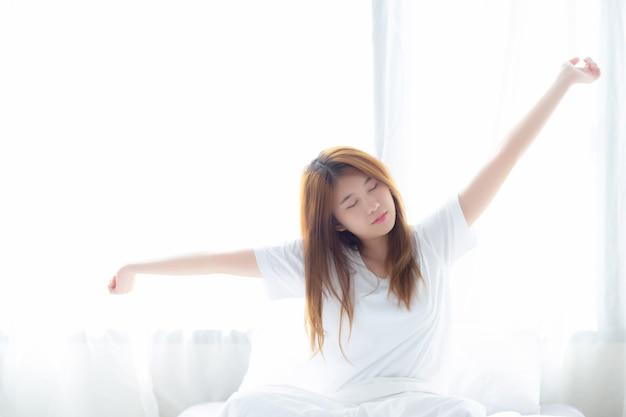 De mooie aziatische vrouwenrek en ontspant in bed Premium Foto