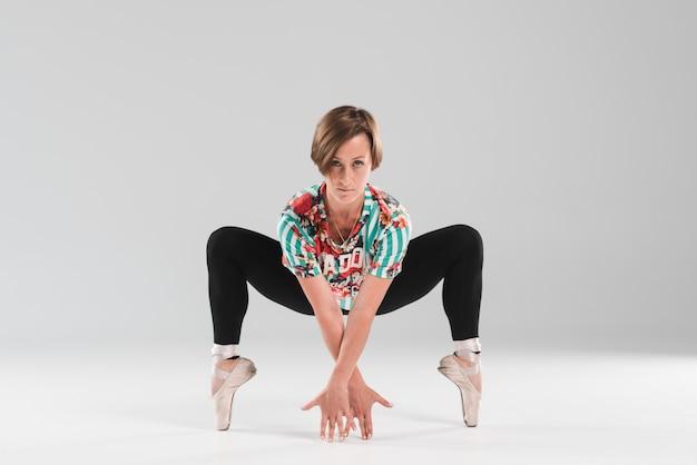 De mooie ballerina danst op de uiteinden van de tenen op grijze achtergrond Gratis Foto