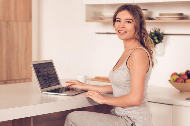 De mooie bedrijfsvrouw in huiskleren gebruikt laptop Premium Foto