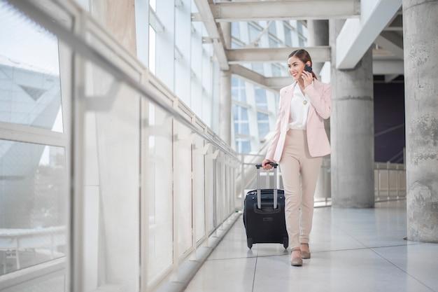 De mooie bedrijfsvrouw loopt in luchthaven, bedrijfsreisconcept Premium Foto