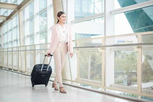 De mooie bedrijfsvrouw loopt in luchthaven Premium Foto
