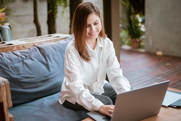 De mooie bedrijfsvrouw werkt met haar laptop computer in koffiewinkel Premium Foto
