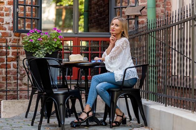 De mooie blonde vrouw kleedde zich in lichte kleren zittend in openluchtkoffie en nippend aan een cocktail Premium Foto