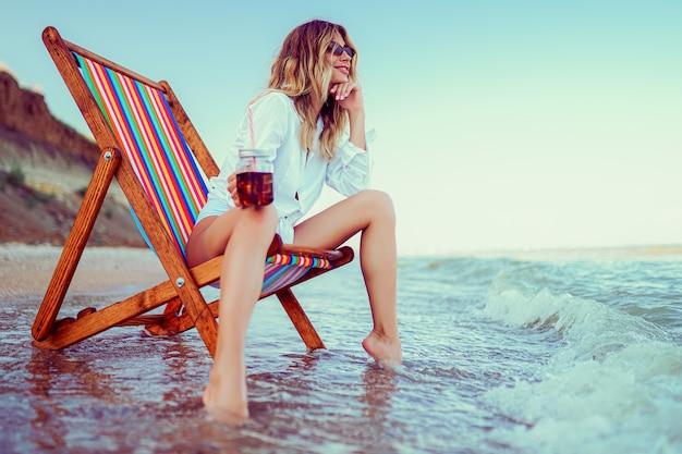 De mooie blondevrouw in de vorm van een hartzonnebril, een wit overhemd en een gestript zwempak die op een ligstoelstrand ontspannen en drinkt coctail. zomervakantie concept Premium Foto