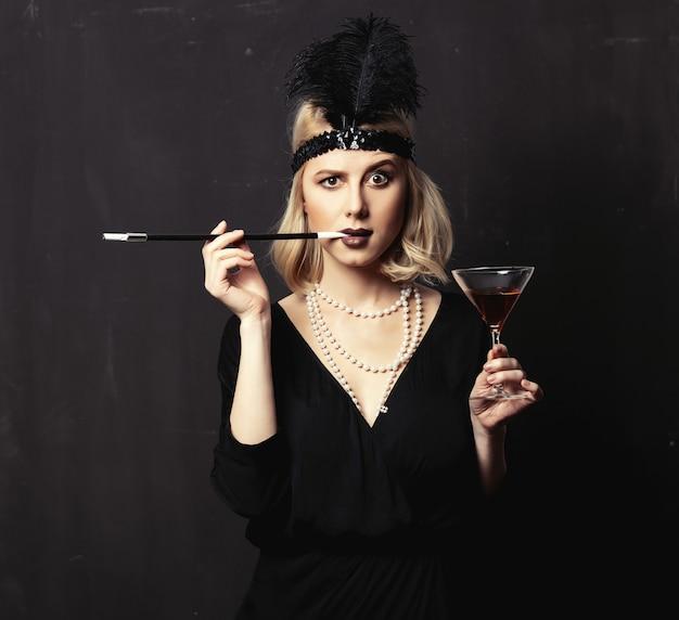 De mooie blondevrouw in jaren 20 kleedt zich met rokende pijp en cocktail op donkere achtergrond Premium Foto