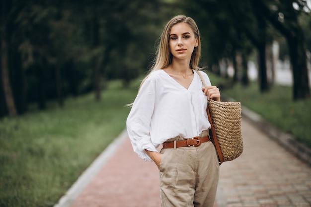 De mooie blondevrouw in park die de zomer draagt ziet eruit Gratis Foto