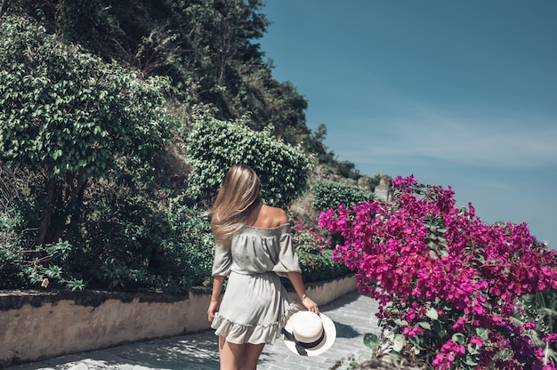 De mooie blondevrouw loopt en bewondert tropische landschappen bij het hotel van het paradijseiland in sanya, china. Premium Foto