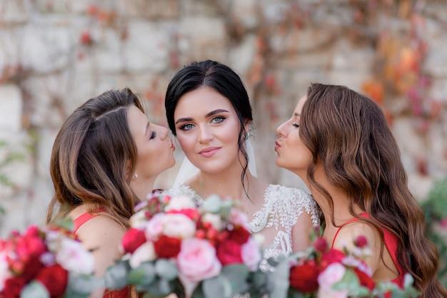De mooie donkerbruine bruid met blauwe ogen kijkt recht en de bruidsmeisjes kussen bijna in openlucht op de wangen met rode rooskleurige vage voorgrond Gratis Foto