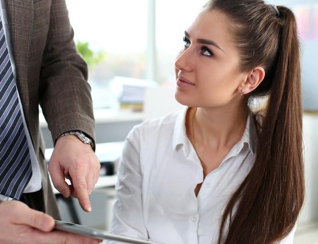 De mooie donkerbruine vrouw gebruikt tabletpc in bureau Premium Foto