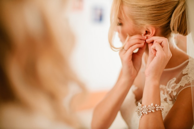 De mooie elegante bruid draagt oorringen in de ochtend op haar weddig dag Premium Foto