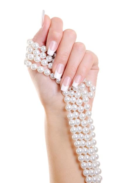 De mooie elegante vrouwenhand met franse manicure houdt de witte perl over Gratis Foto