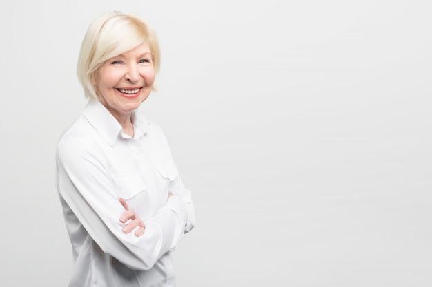 De mooie en zekere oude vrouw bevindt zich aan de rechterkant van frame haar handen gekruist houden en vol vertrouwen glimlachen. ze ziet er geweldig en vrouwelijk uit op haar leeftijd. Premium Foto